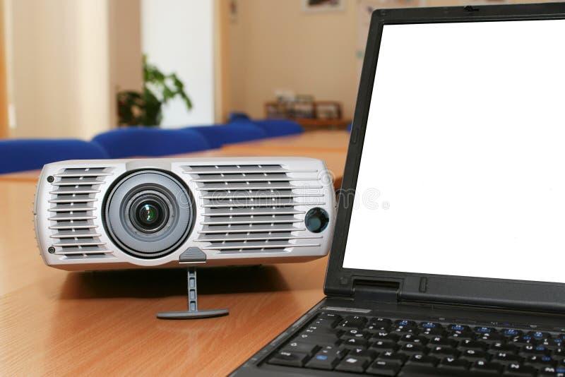 Laptop mit dem Projektor auf Bürotabelle stockfoto