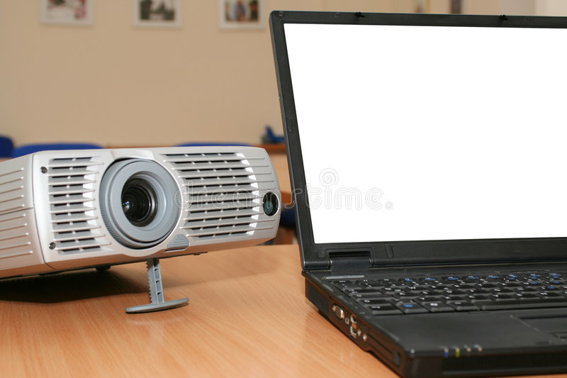 Laptop mit dem Projektor auf Bürotabelle lizenzfreie stockbilder