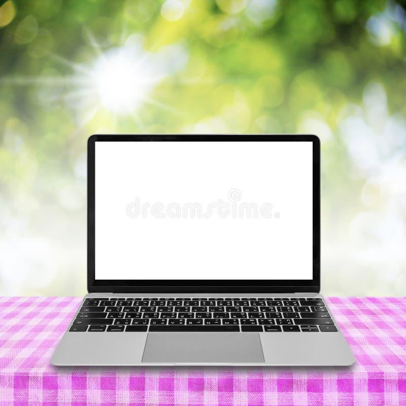 Laptop mit leerem Bildschirm auf Tabelle mit abstraktem grünem Hintergrund lizenzfreie stockbilder