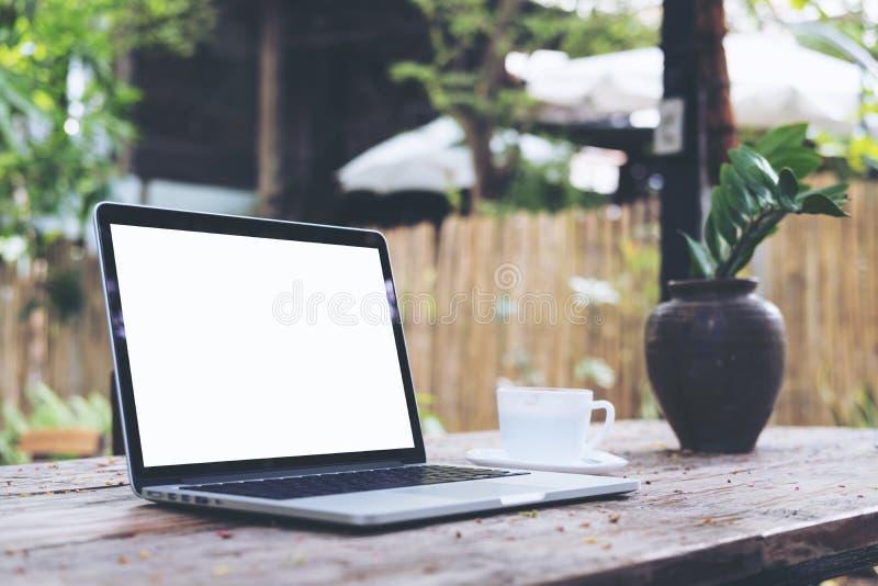 Laptop mit leerem weißem Schirm und Kaffeetasse auf Weinleseholztisch Park der Natur im im Freien lizenzfreie stockbilder