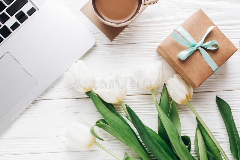 Laptop mit Morgenkaffee und Tulpen und stilvolle Geschenkbox auf wh stockbild