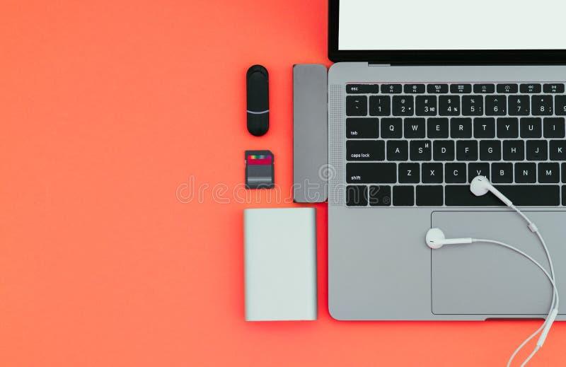 Laptop mit USB-Art-c Adapter, grelle Antriebe, Kopfhörer und Energie-Bank auf einem roten Hintergrund, Draufsicht, Arbeitsplatz lizenzfreies stockfoto