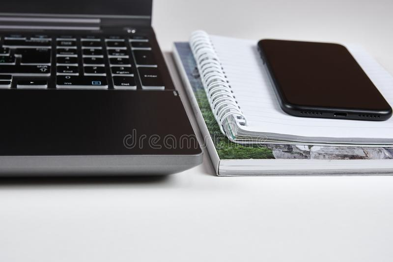 Laptop with mobile phone lying on a paper workbook, on a white t. Able - with a blurred background stock photography