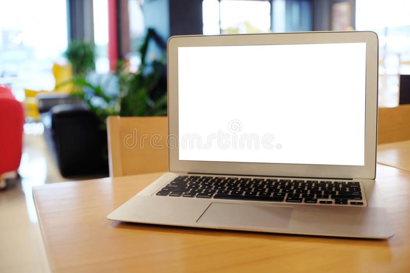 Laptop with Mock up blank screen on wooden table in front of coffeeshop cafe space for text. product display montage- technology. Concept stock photo