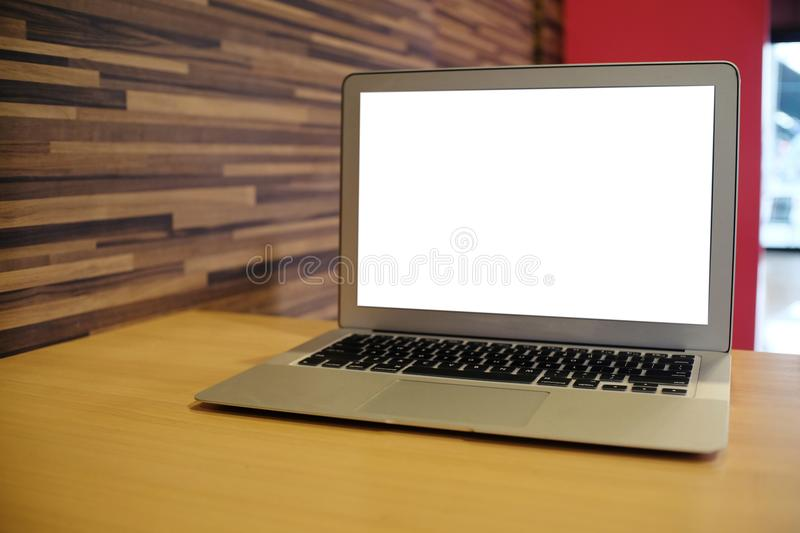Laptop with Mock up blank screen on wooden table in front of coffeeshop cafe space for text. product display montage- technology. Concept stock image