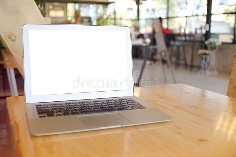 Laptop with Mock up blank screen on wooden table in front of coffeeshop cafe space for text. product display montage- technology. Concept royalty free stock photo