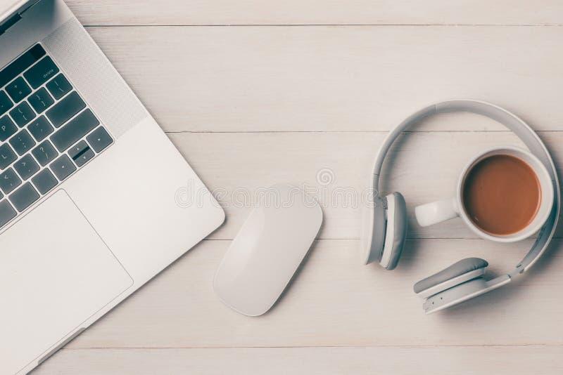Laptop na bielu stole z hełmofonem i filiżanką vi obraz stock