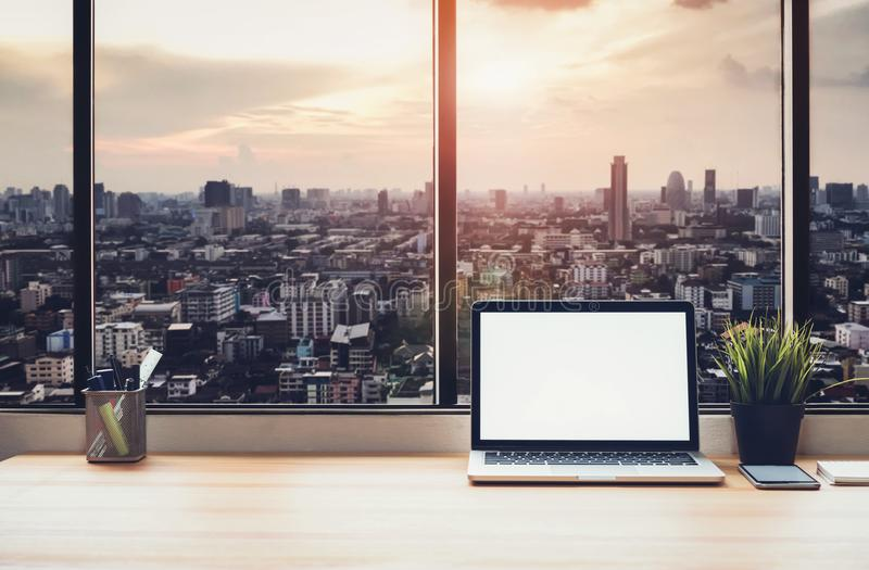 Laptop na stole w biurowym pokoju na nadokiennym miasta tle dla grafika pokazu montażu, zdjęcie stock