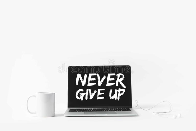 Laptop with Never give up inspiration on screen, earphones and white mug, isolated on white royalty free stock photography