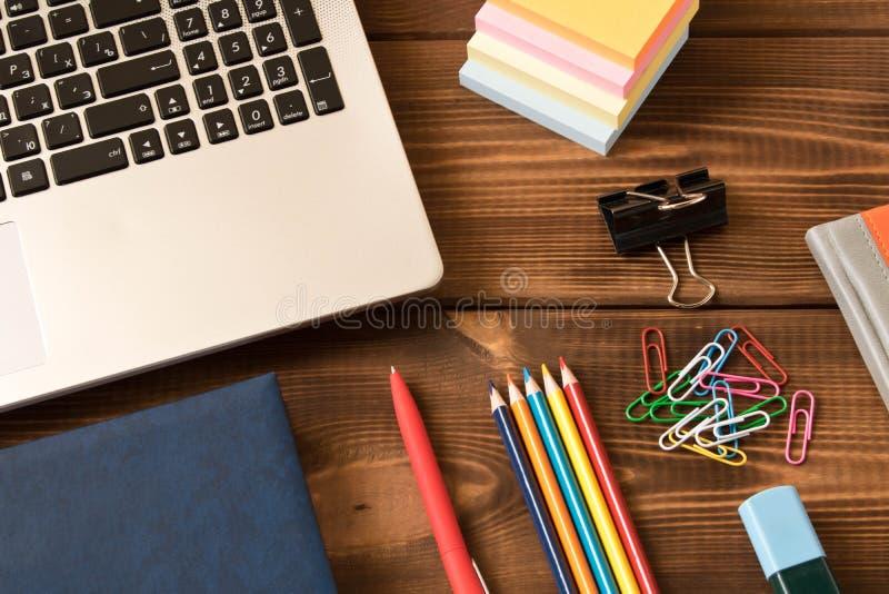 Laptop, notatnik, pi?ro, o??wki na drewnianym stole R??norodne biurowe dostawy na drewnianym tle fotografia stock