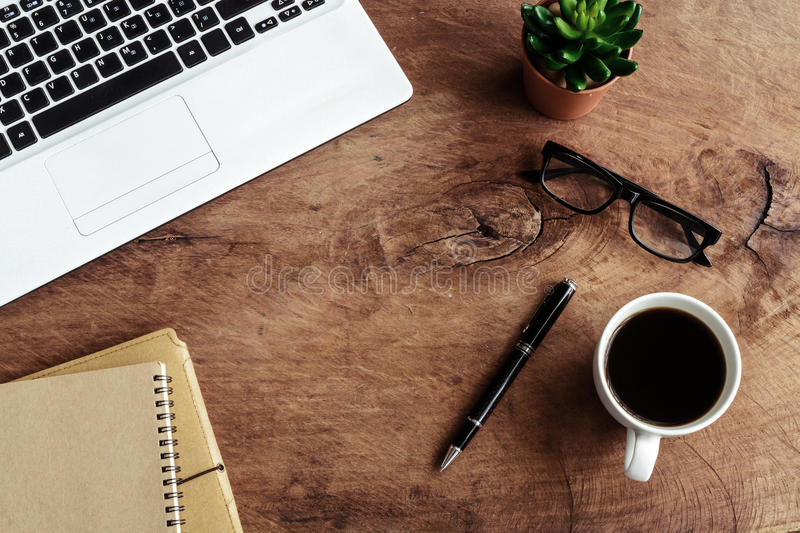 Laptop with notebook and cup of coffee on old wooden table royalty free stock photos