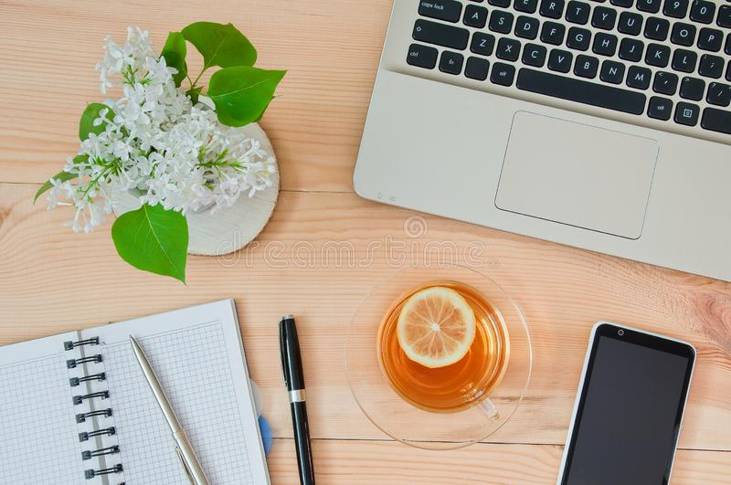 Laptop, notebook with a pen, cup of tea and a  bouquet of white flowers on the desktop. Business concept royalty free stock photos