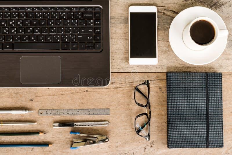 Laptop, Notitieboekje, Telefoon, Koffie, Glazen, Pen en Potlood op Houten Bureau royalty-vrije stock afbeeldingen