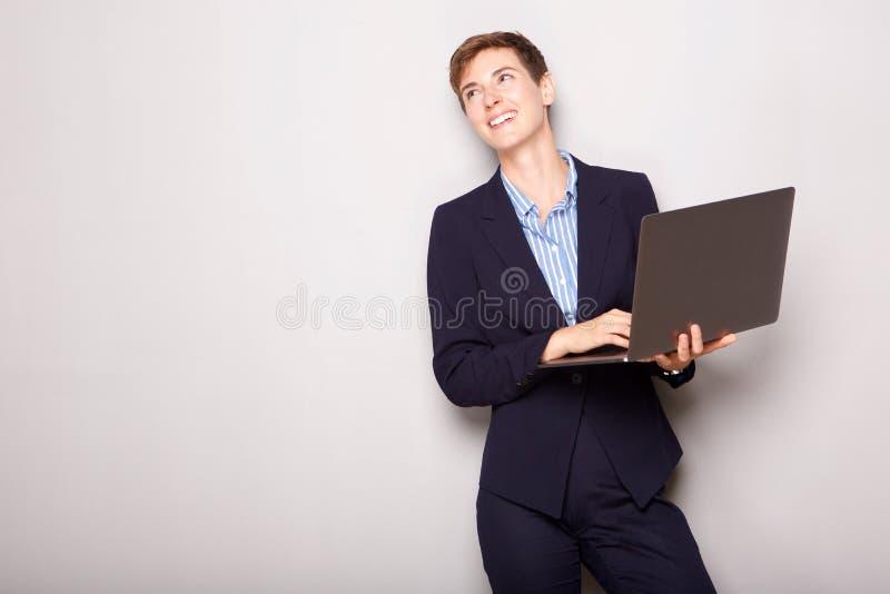Laptop novo feliz da terra arrendada da mulher de negócios foto de stock royalty free