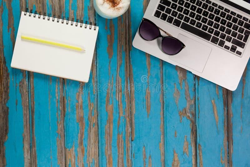 Laptop, okulary przeciwsłoneczni, kawowy kubek, notepad i ołówek, fotografia royalty free