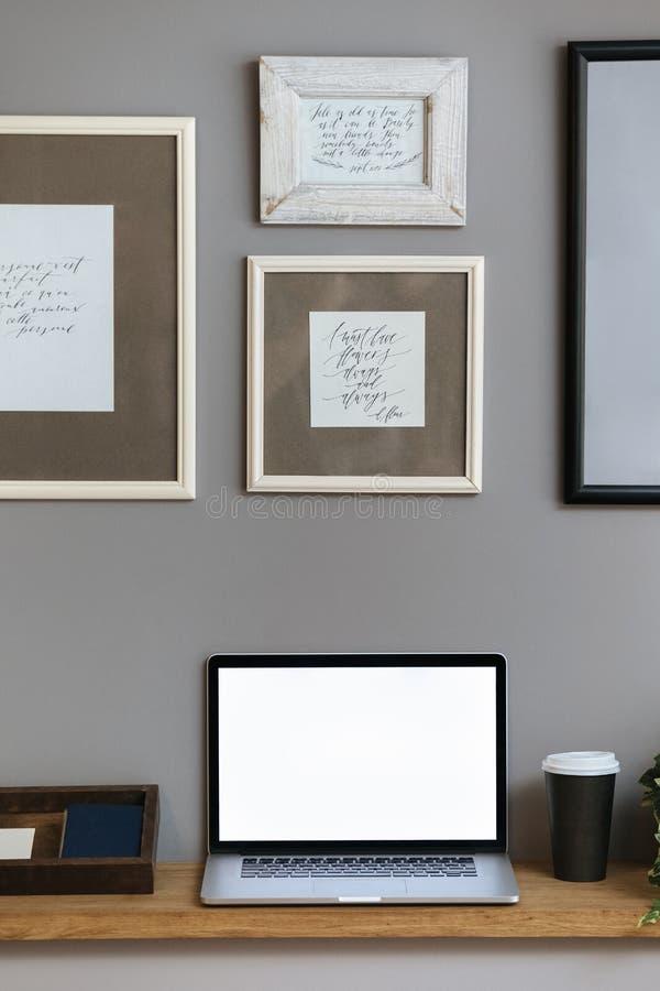 Laptop op houten lijst, grijze muur royalty-vrije stock afbeeldingen