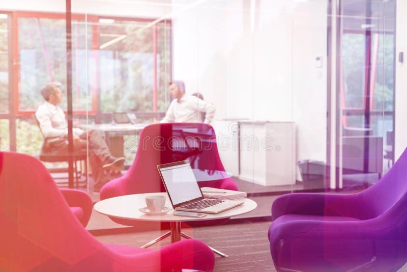 Laptop op lijst door stoelen in bestuurskamer met zakenlieden die op achtergrond bespreken stock afbeelding