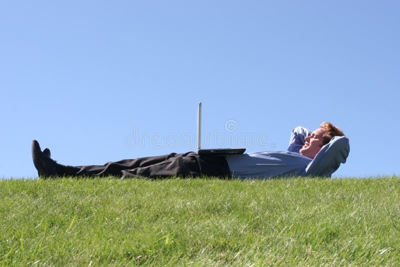 Laptop op zakenman op gras stock foto's