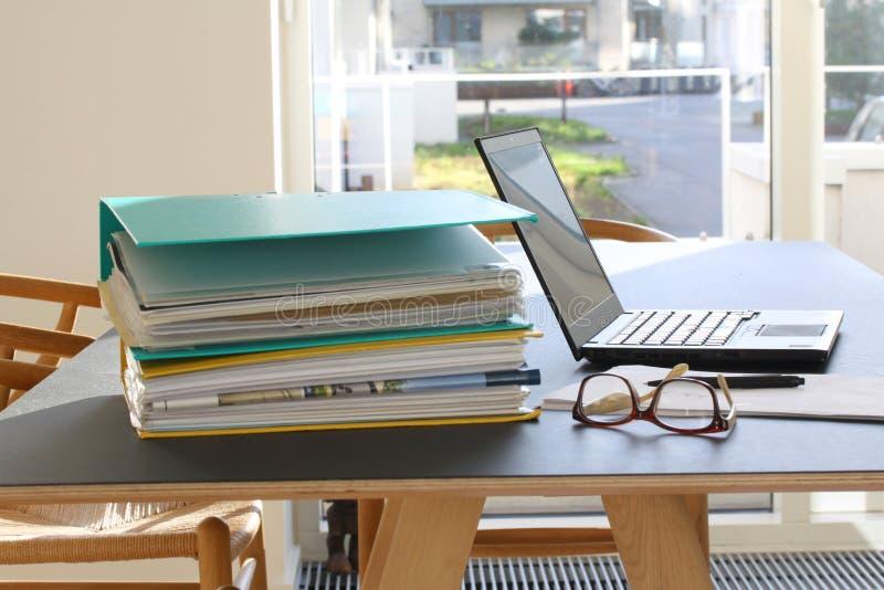 Laptop, pastas de anel enchidas com os papéis, folhas do vidro, as de papel e lápis na tabela do escritório Foco seletivo fotografia de stock royalty free