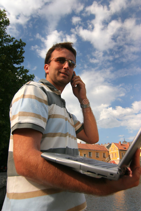 Laptop & phone. Handsome man with phoning, laptop stock photo