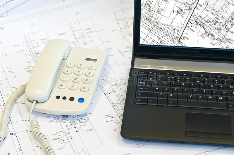 Laptop, phone on project drawings. royalty free stock photo