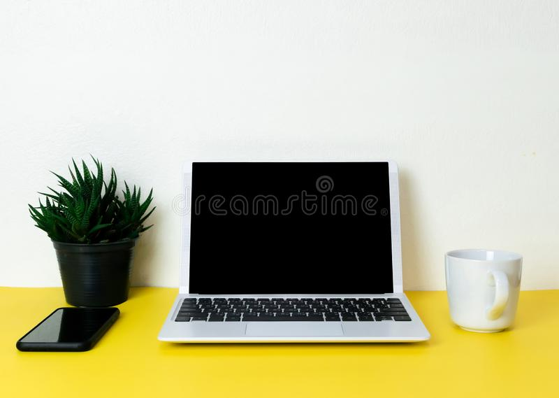 Laptop placed on a yellow table background of business working place with cup coffee stock photos
