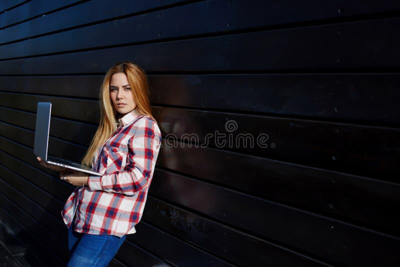Laptop portátil do uso na moda novo do estudante no terreno fotografia de stock royalty free