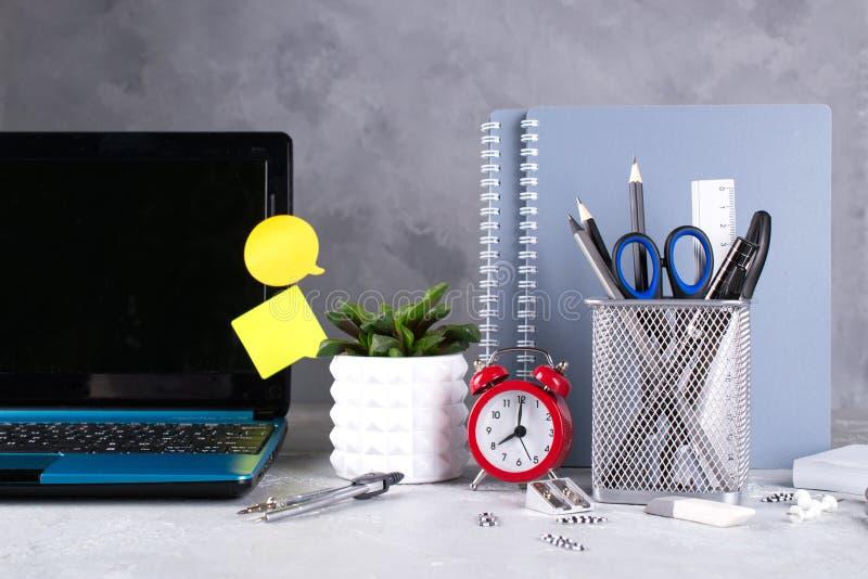 Laptop, red alarm clock and supplies on a gray concrete desk. stock photos