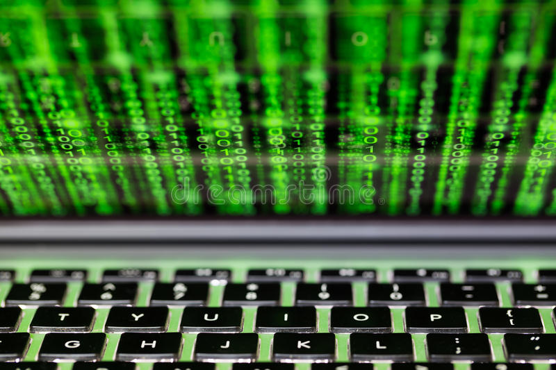 Laptop screen with binary code cybersecurity concept. Laptop screen and keyboard with green binary matrix code closeup cybersecurity concept royalty free stock image