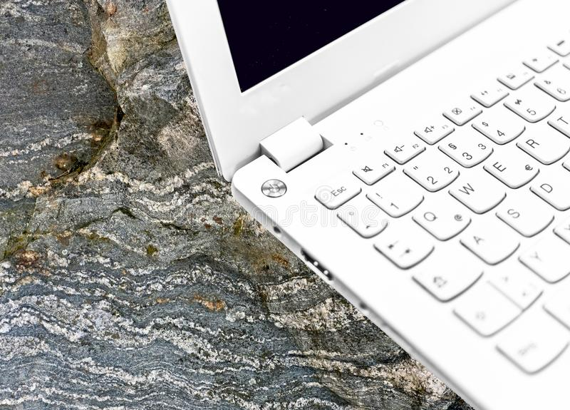 Laptop, shot with low depth of field, on a gneiss from the Palaeozoic period. stock image