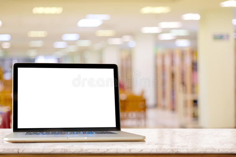 Laptop showing blank screen on marble table. Mock up Laptop marble top table and blurred co-working or cafe background. Blank screen for graphis display montage royalty free stock images