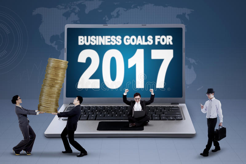 Laptop showing text of business goals for 2017. Busy business team and a big portable computer showing text of business goals for 2017 with world map on the royalty free stock images
