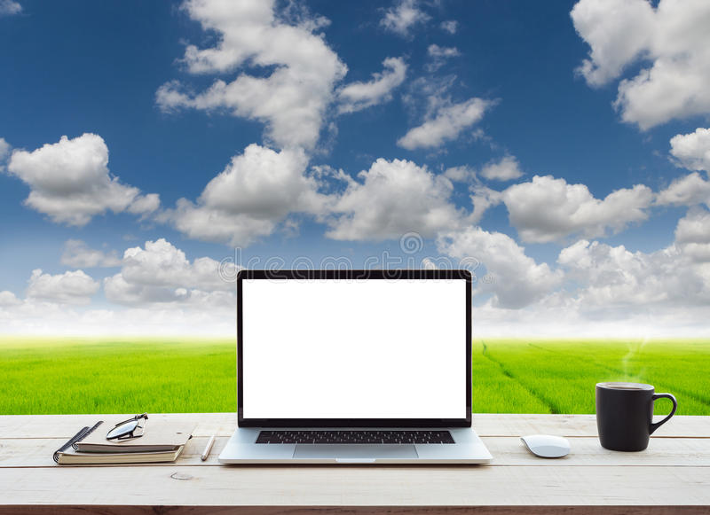 Laptop showing white screen on work table meadow and bl royalty free stock photography