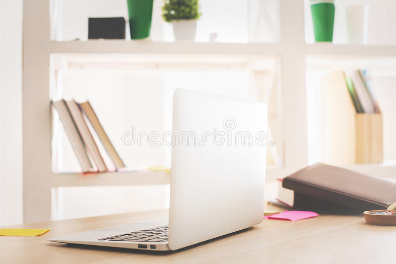 Laptop side. Side view of open laptop placed on wooden office desktop with book, supplies and other items stock image