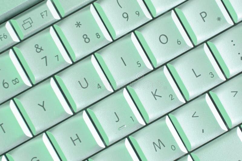 Laptop sleutels in groen licht stock foto's