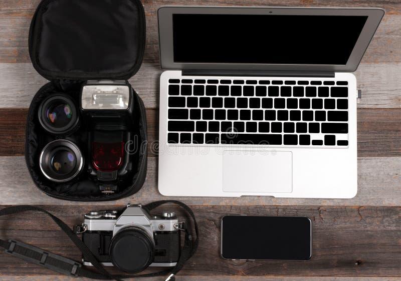 Laptop, slimme telefoon, fotocamera en hoofdtelefoon op houten achtergrond royalty-vrije stock foto's