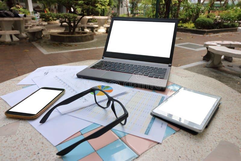 Laptop, Smartphone, Gläser und Diagramme auf Marmorplatte im Park stockbilder
