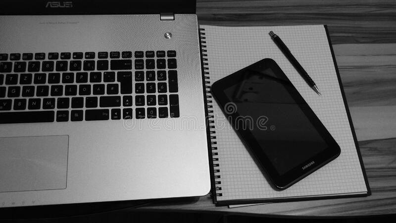 Laptop smartphone and notebook on table stock image