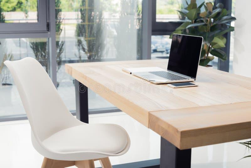 Laptop, Smartphone und leere Papiere auf Arbeitsplatz im leeren Büro lizenzfreies stockfoto