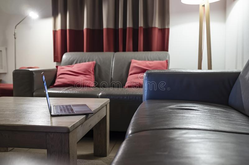 Laptop stands on a wooden table, next to two leather sofas, in a cozy home interior with a illuminated floor lamp, which disposes. Laptop stands on a powerful royalty free stock image