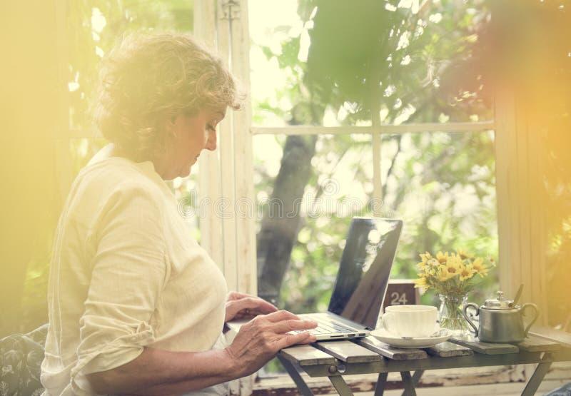 laptop starsza używa kobieta fotografia stock