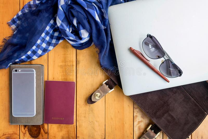 Leather bag notebook and blue check scarf on wood table stock photo