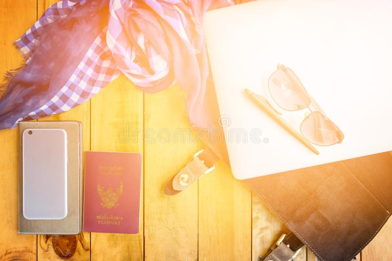 Leather bag notebook and blue check scarf on wood table royalty free stock photography