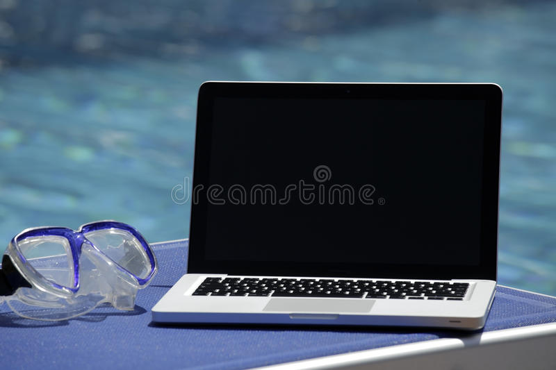 Laptop by swimming pool stock images
