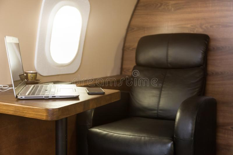 Laptop on the table in the interior of a private jet. Flying first class. Laptop on the table in the interior of a private jet. Flying first class royalty free stock photo