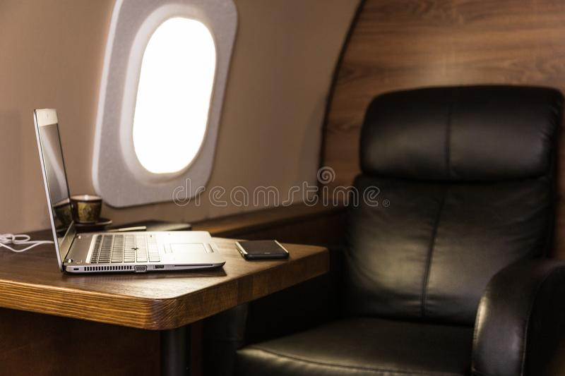Laptop on the table in the interior of a private jet. Flying first class. Laptop on the table in the interior of a private jet. Flying first class stock photos
