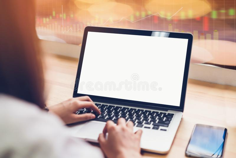 Laptop on table in office room on stock exchange trading graph for background, for graphics display montage. stock images