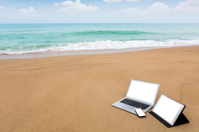 Laptop ,tablet and smartphone on the beach royalty free stock photos