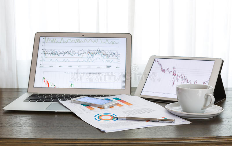 Laptop, tablet , smartphone and coffee cup with financial documents on wooden table stock image