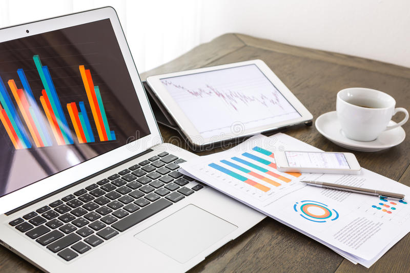 Laptop, tablet ,smartphone with financial documents on wooden table royalty free stock image